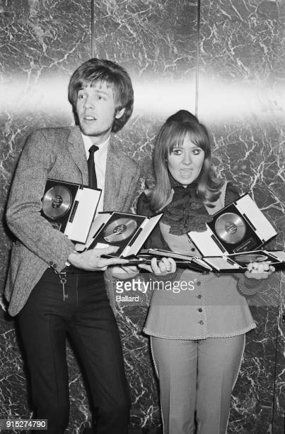 British singersongwriter Lulu with BritishAmerican singersongwriter composer and record producer Scott Walker hold the awards they have received at...