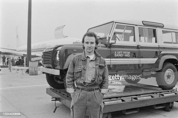 British singer-songwriter Midge Ure poses, hands in pockets, with a Land Rover Defender - 'A Gift From Band-Aid' written on the door - as the first...