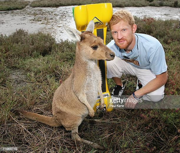 British skate boarder Dave Cornthwaite poses for a photo with a kangaroo at Heirisson Island on August 18 2006 in Perth Australia The Welshman...