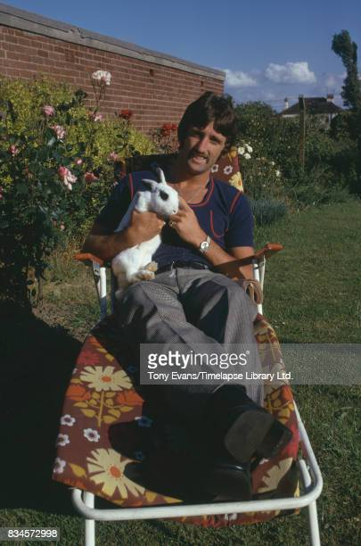 British soccer player David Johnson holds a rabbit while laying down on a deckchair July 1974