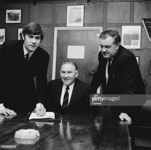 British soccer player Peter Collins signs transfer forms from Chelmsford City FC to Tottenham Hotspur FC with respective managers Harry Ferrier and...
