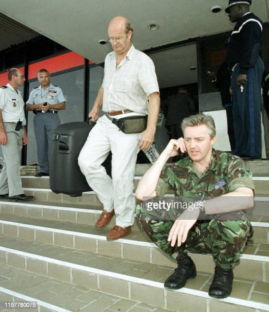 A British soldier chats on a mobile phone 09 May 2000 as a European arrives from Freetown Sierra Leone at the airport in Dakar The evacuation of...