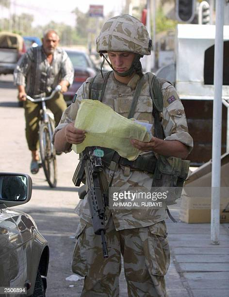A British soldier checks the papers of a car at a checkpoint in the southern Iraqi city of Basra 11 September 2003 Britain will send at least another...