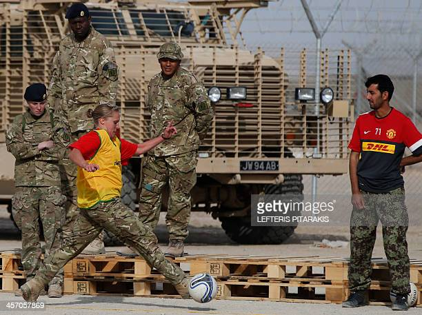 British soldier controls the ball during a soccer match as comrades and an Afghan National Army soldier look on during a soccer training session and...