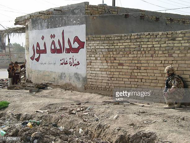 A British soldier crouches while on a patrol in the town of Amarah to the north of Basra as Iraqi children watch Shiite Muslim warlords and militias...