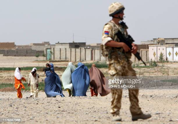 A British soldier from 16 Air Assault Brigade holds his rifle as women in burkas walk past during a foot patrol in Lashkar Gah Helmand province 16...