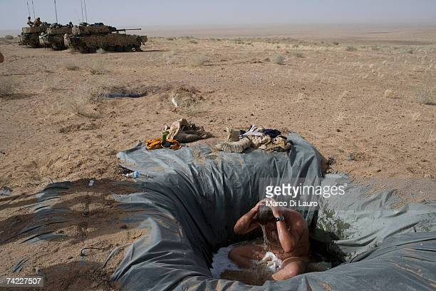British soldier from the B Squadron of the Light Dragoons Regiment takes his first bath in two weeks in a location in the desert while conducting...