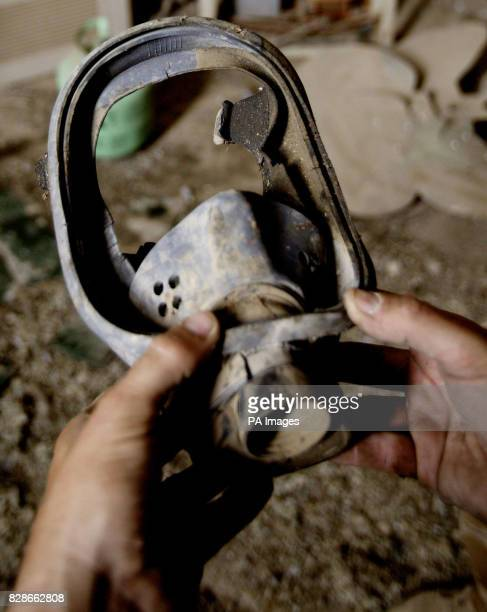 A British soldier from the REME examines the remains of a gas mask found at a building believed to have been used by 'Chemical Ali' as his...