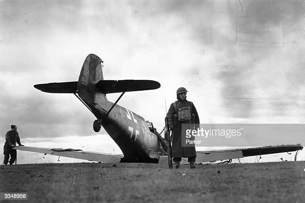 British soldier guarding a German Messerschmitt Bf 109 fighter plane, which was intercepted over the English Channel and shot down by a Spitfire...
