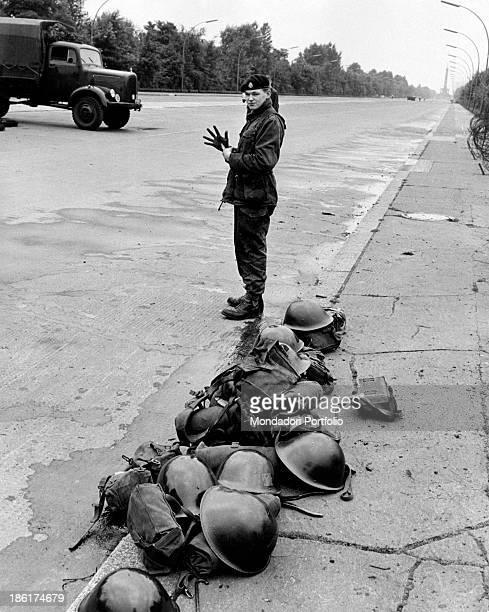 A British soldier guarding the Strasse des 17 Juni beside a heap of helmets n the distance the Victory Column in Tiergarten West Berlin August 1961