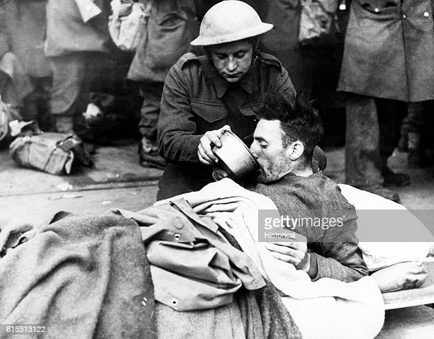 A British soldier helps a wounded man drink while waiting to be evacuated from Dunkirk France in June 1940 British and French troops were forced to...