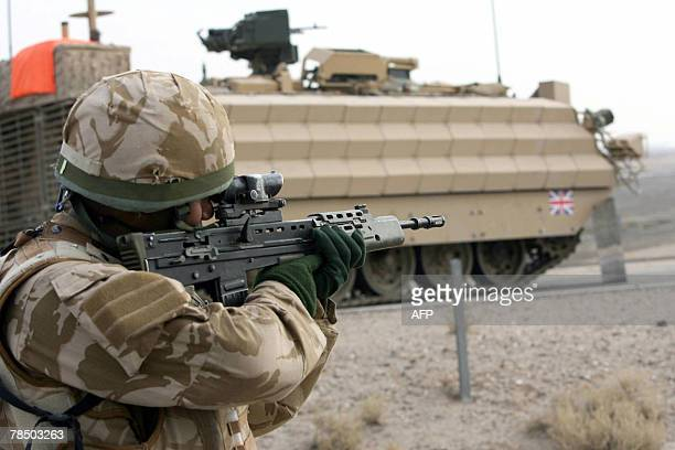 A British soldier keeps watch as an armoured vehicle drives by on the road around the airport ahead of the security transfer from British troops to...