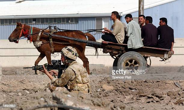 British soldier keeps watch while men ride in a horse cart out of the city April 5, 2003 in Basra, Iraq. British forces have slowly been advancing on...