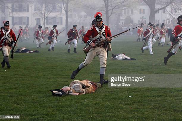 British soldier kicks an injured Patriot as British run back across the Lexington Green after battling with Minutemen during an reenactment of the...