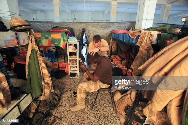 British soldier LCpl Roy Gale helps cut Private Jeremy Alexander's hair as they rest in their accommodation at the 50 Brigade MiTT at the Iraqi naval...