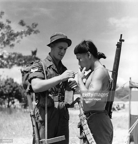 A British soldier lighting a cigarette for a Dyak during the campaign in Malaya to get rid of Communist bandits Original Publication Picture Post...