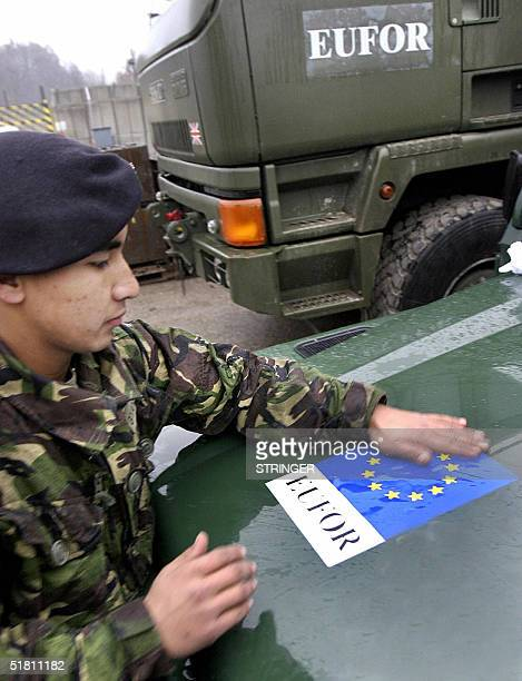 British soldier member of NATOled peacekeeping Stabilization force for Bosnia and Hercegovina affixes new EUFOR stickers to his vehicles in military...