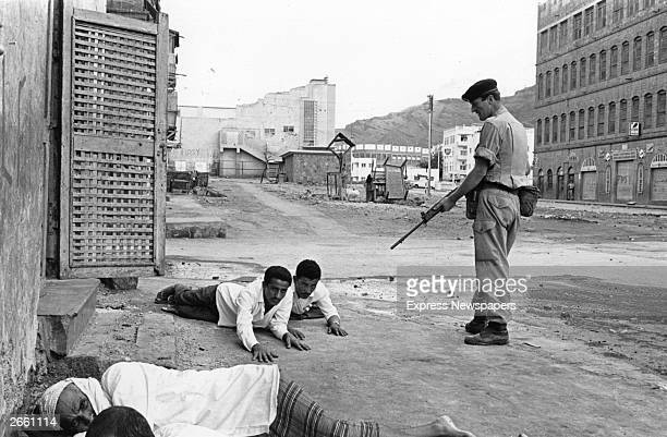 A soldier of the Northumberland Fusiliers threatening Arab demonstrators in Crater Aden