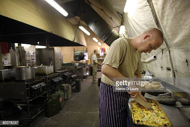 British soldier on duty as a chef prepares lunch at the British Army base Task Force Helmand Headquarter on July 23 2008 in Lashkar Gah Helmand...
