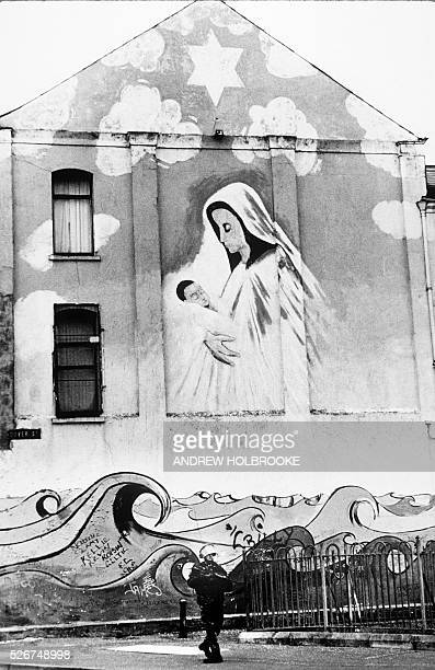 British soldier on patrol along the Falls Road in West Belfast passes a wall mural of the Madonna and child.