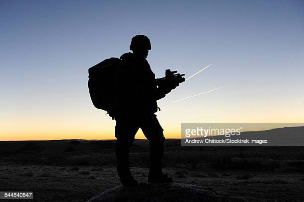 A British soldier on patrol as the Sun rises at Sennybridge Training Area, Wales, United Kingdom.