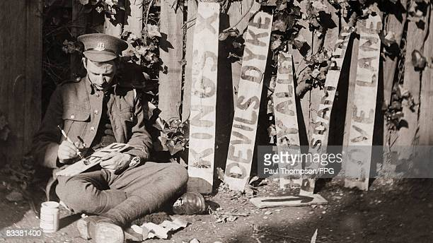 A British soldier paints the names of various World War I trenches on wooden signs circa 1915 The names include King's Cross Devil's Dyke Happy Alley...