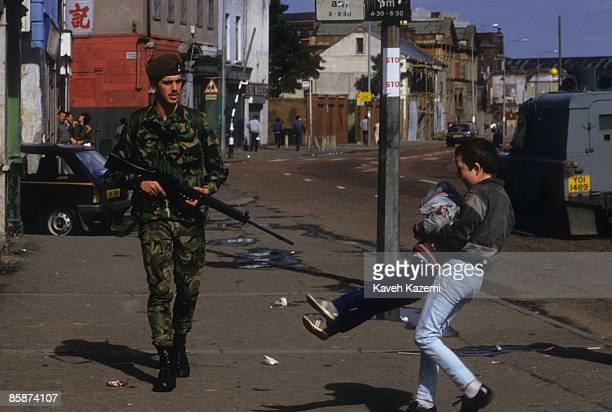 A British soldier passes two boys playing on the street during a routine patrol on the Falls Road in Catholic west Belfast Northern Ireland 18th...
