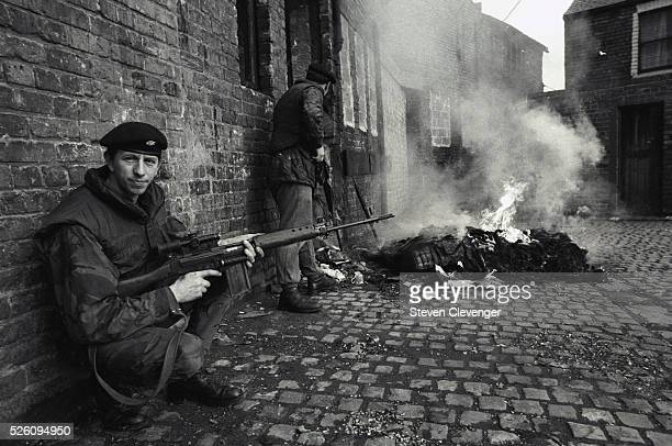 A British soldier provides cover for his fellow soldiers while they check out a burning building The IRA was known to set fire to a building and wait...