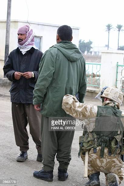 British soldier searches 12 January 2004 an Iraqi man at a bridge near the government buildings as tensions remained high in the southern city of...