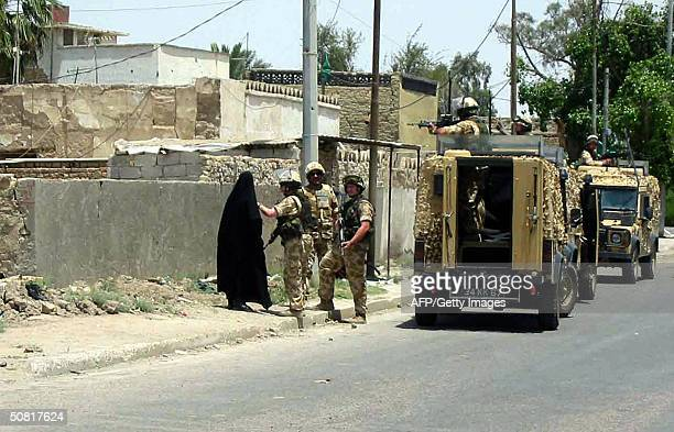 British soldier searches an Iraqi woman during a patrol in the southern city of Basra 09 May 2004 Three British soldiers were wounded as an explosive...