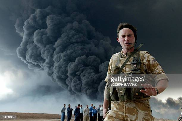British soldier secures an area near the burning oil export pipeline from the southern city of Basra, 500 kilometres from Baghdad, to the Faw...