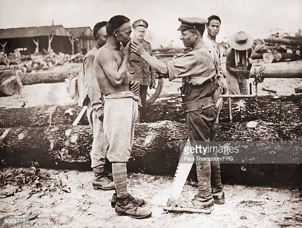 A British soldier shares a cigarette with a Chinese labourer in France during World War I circa 1916