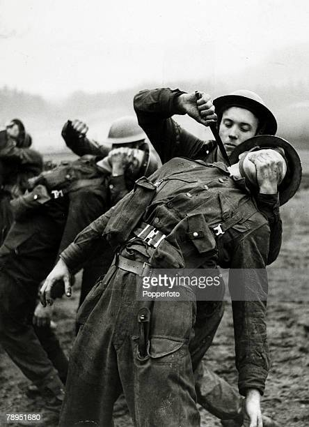 circa 1940 Commando training in Scotland as a British soldier shows how to attack a man from behind using a knife