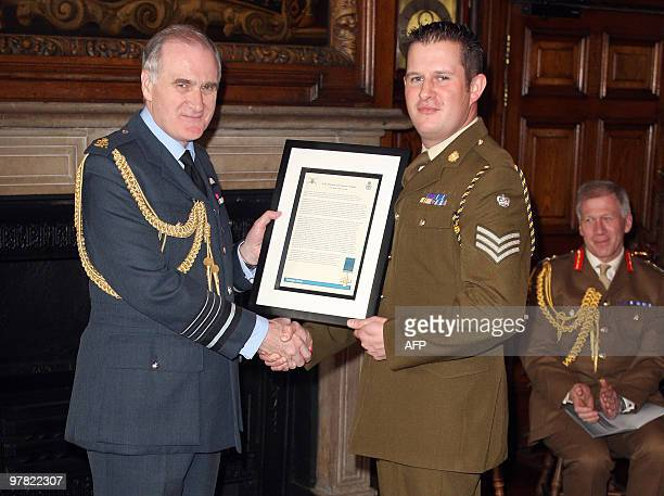 British soldier Staff Sergeant Kim Hughes receives the George Cross citation from Chief of the Defence Staff Air Chief Marshal Sir Jock Stirrup at a...