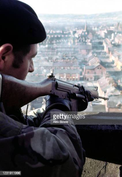 A British soldier takes aim at a suspect from an army Observation Post located on the roof of a highrise tower block in the republican New Lodge...