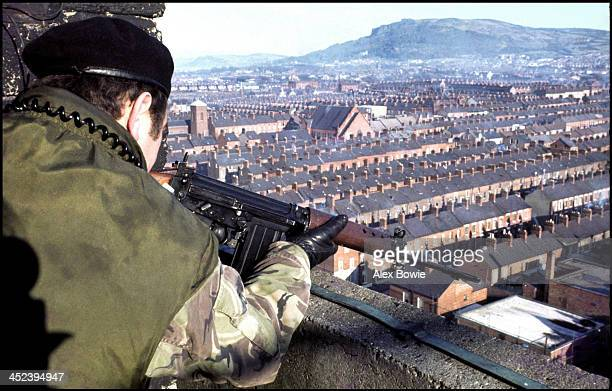 A British soldier takes aim at a suspect from an army Observation Post located on the roof of a council tower block overlooking the republican New...