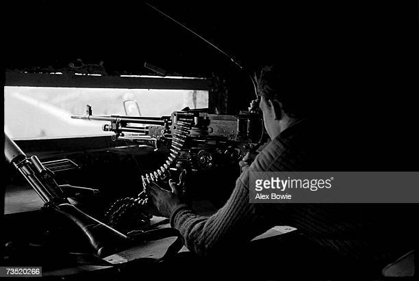 A British soldier trains his GPM machine gun on an alley often used by IRA snipers to target foot patrols returning to the military base located in...