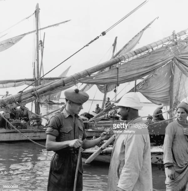 A British soldier uses hand gestures to communicate with an Egyptian boat owner during the Suez Crisis 15th November 1956