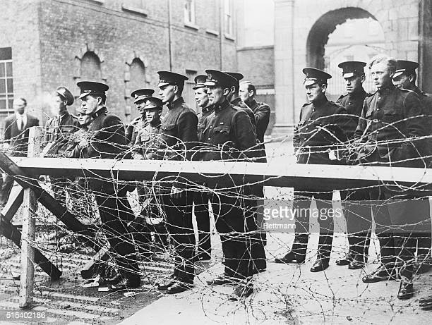 British soldiers and Irish soldiers of the Royal Irish Constabulary watch fighting at the Four Courts across the River Liffey from their station at...