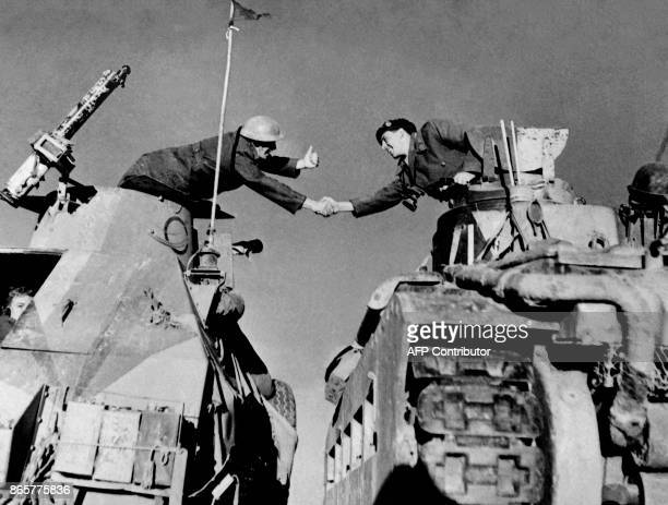 British soldiers belonging to the Commonwealth and Allied forces shake hands while progressing in October 1942 in the desert of Tobruk seaport in...