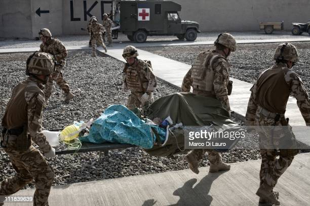 British soldiers carry on a stretcher from the MERT CH-47 Chinook helicopter a nine years old Afghan child into an ambulance to transfer him to a...