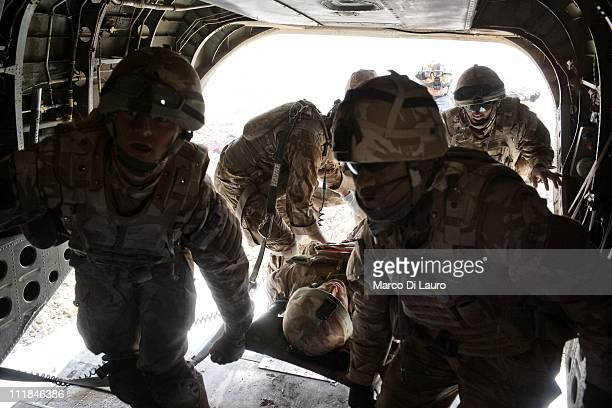 British soldiers carry on a stretcher into the British Royal Air Force MERT CH-47 Chinook helicopter two fellows British soldiers on November 26,...