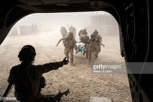 British soldiers carry on a stretcher into the MERT CH47 Chinook helicopter a nine years old Afghan child on November 28 2009 in Helmand Province...