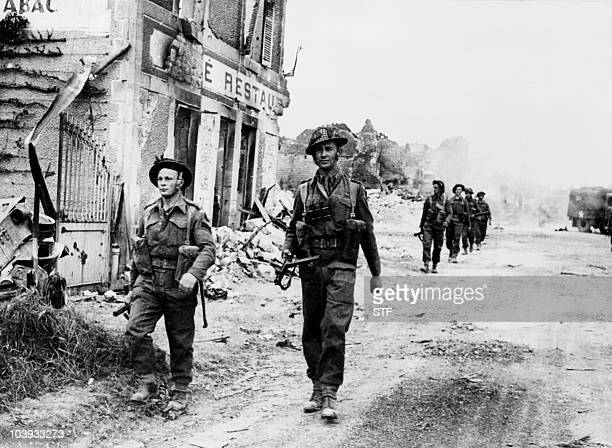 British soldiers cross 08 June 1944 the village of Douet after the town of Bayeux fell after Allied forces stormed the Normandy beaches DDay 06 June...
