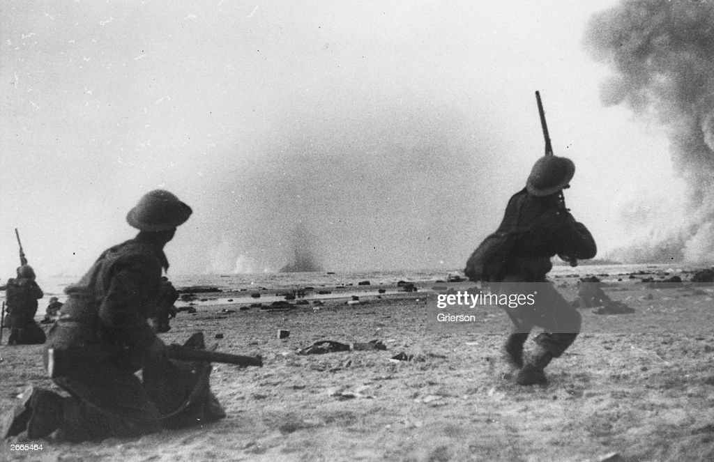 British soldiers fight a rearguard action during the evacuation at Dunkirk, shooting rifles at attacking aircraft. Bombs are exploding in the sea.