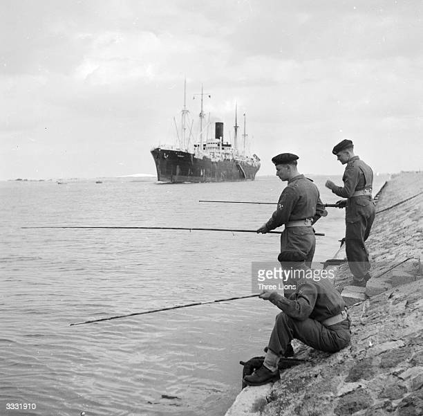 British soldiers fishing in the Suez Canal while stationed there during the Suez crisis
