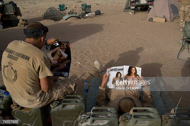 British soldiers from the B Squadron of the Light Dragoons Regiment read magazines in a location in the desert while conducting counterTaliban...