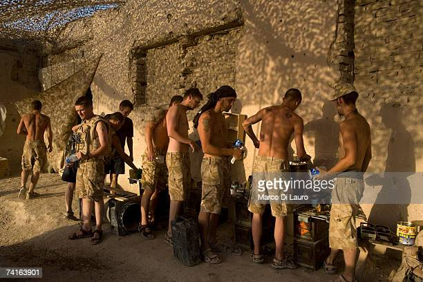 British Soldiers from the Grenadier Guards line up to collect food cooked by one of them to break the routine of the military rations on May 14 2007...