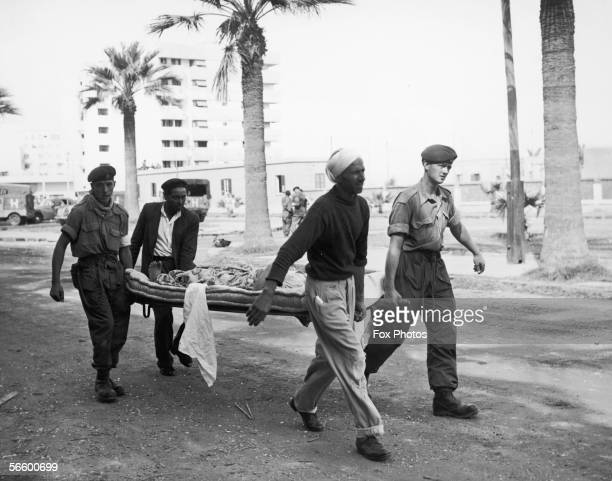 British soldiers help to carry a wounded Egyptian to a first-aid centre in Port Said, during the Suez Crisis, 12th November 1956.