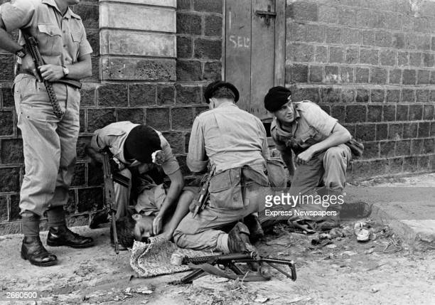 British soldiers helping their wounded colleague after he had been injured by a hand grenade in Aden during nationalist terrorist attacks aiming to...